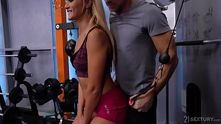 Sporty bitch Cherry Kiss works on two erected cocks in the gym